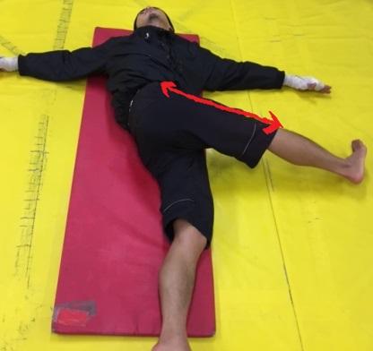 床に寝ころんで足を捻る大腿筋膜張筋のストレッチ